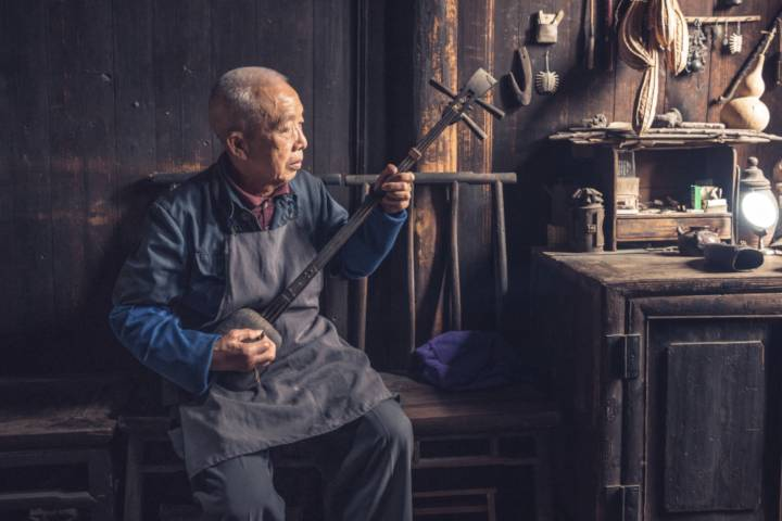 a chinese man is playing a sanxian