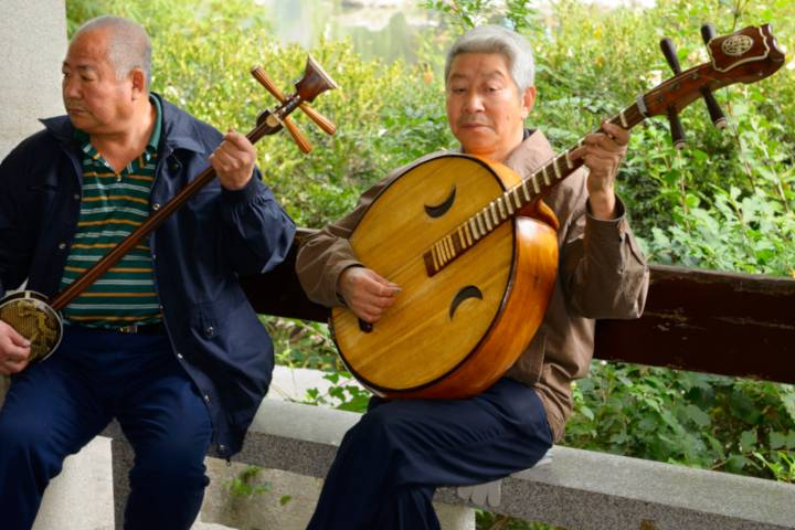 two men are playing a ruan and a sanxian