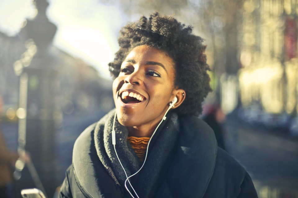 woman smile while listening to music
